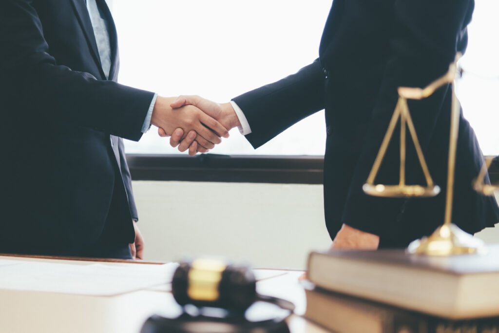 Law and Legal services concept. Lawyer and attorney having team meeting at law firm. Lawyer and businessman handshake.