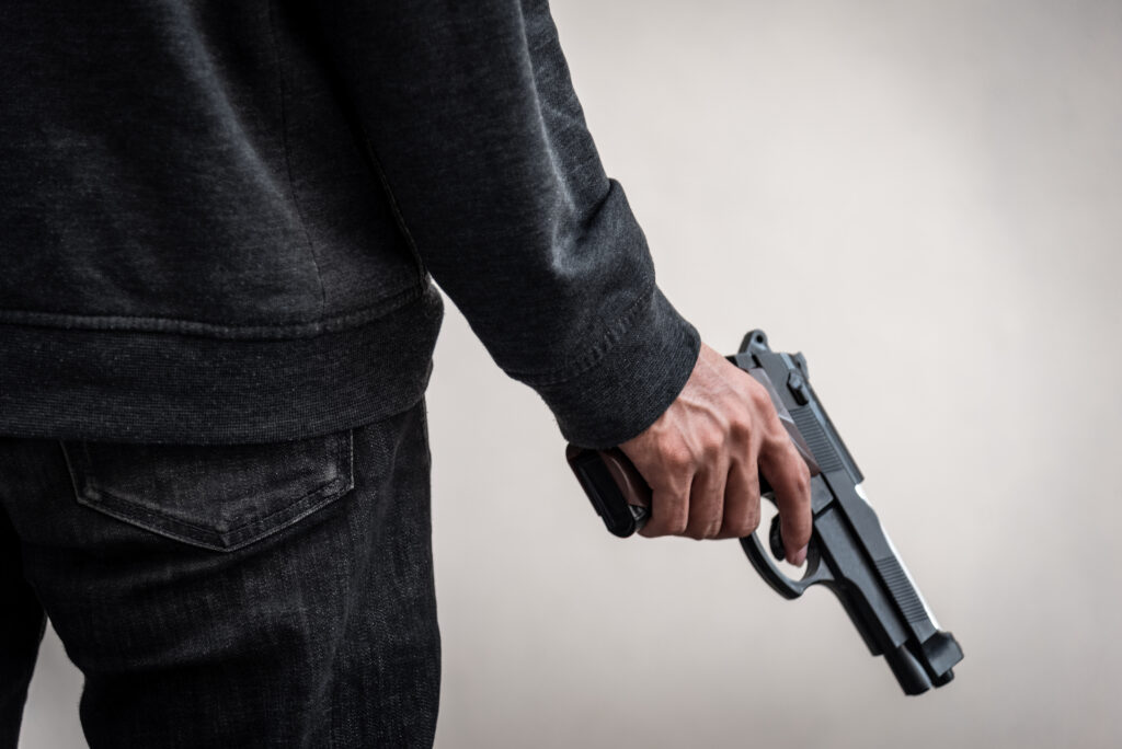 A man holding a gun by his side.